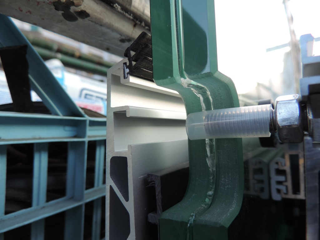 particolare dell'asola nel vetro della pensilina per alloggiare il perno di sicurezza