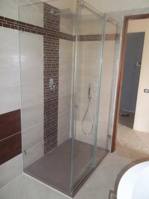 box doccia in cristallo con porta scorrevole e gli altri vetri senza fissaggi con telai perimetralil ma vetro fissato direttamente su piastrelle