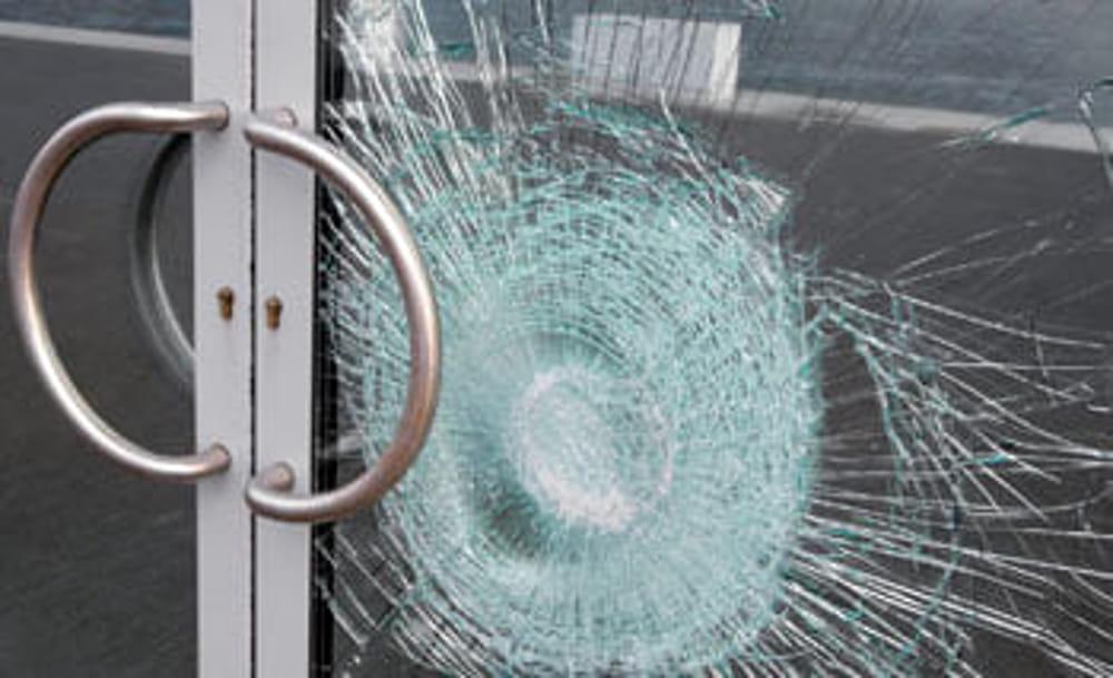 porta di ingresso condominiale con vetro rotto