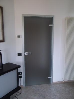 porta in vetro satinato in sostituzione di porta in legno preesistente
