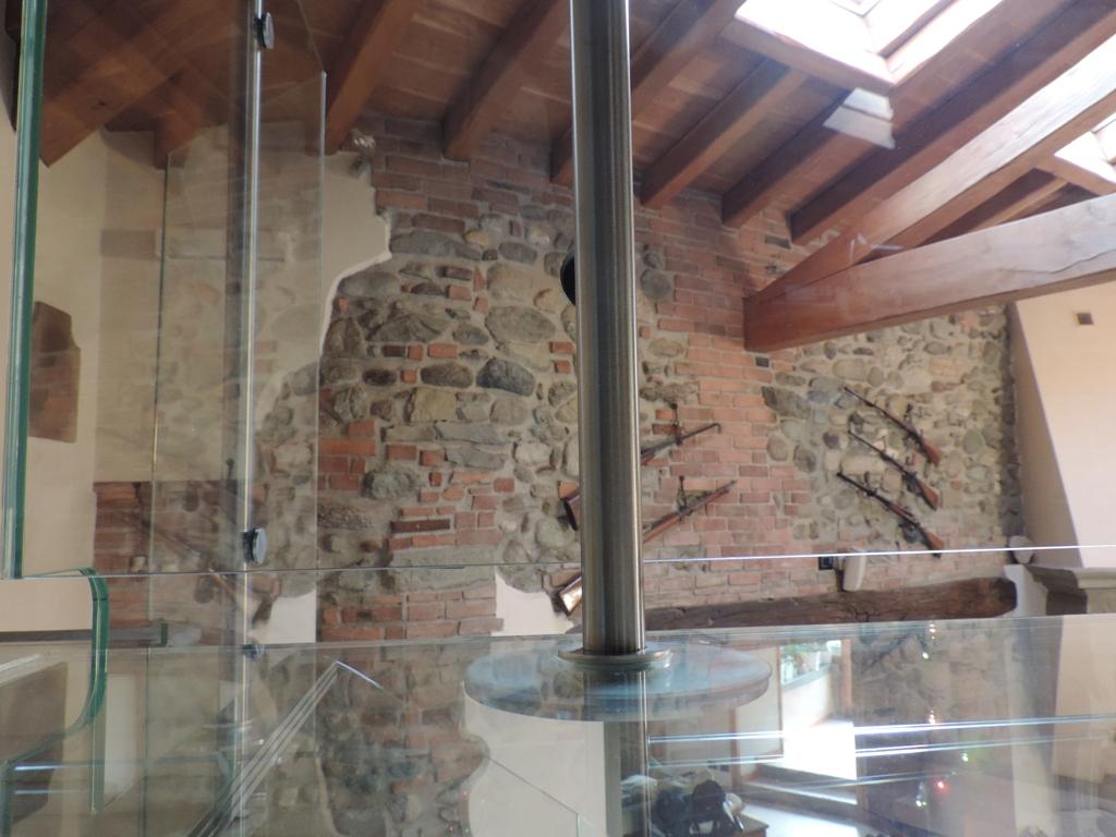 particolare del punto di aggancio del tirante al balcone in vetro