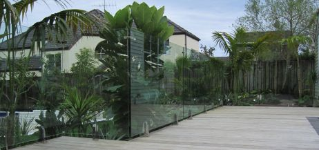 vetro come barriera tra giardino piantumanto e piscina