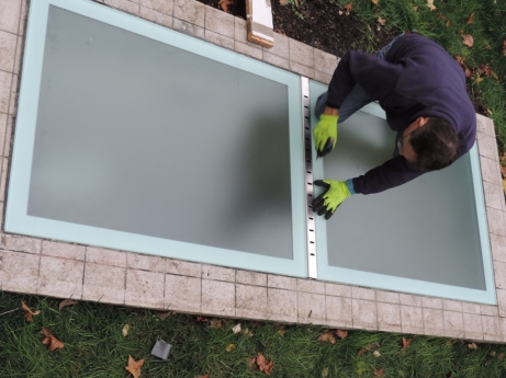 due vetri calpestabili posati con la griglia di drenaggio dell'acqua piovana e di arieggiamento del lucernario del seminterrato