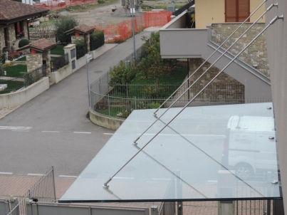 copertura in vetro con tiranti paralleli in acciaio e mensole di sostegno